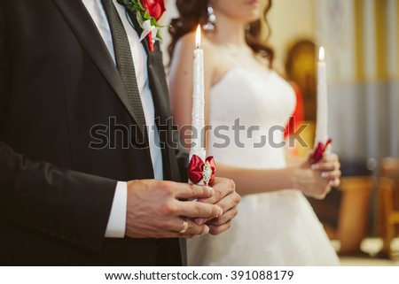 Bride & groom holding candles at wedding ceremony closeup