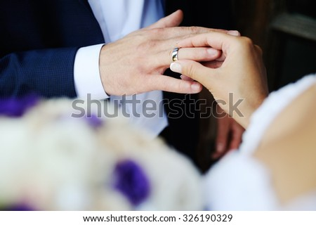 bride groom wears a wedding ring on his finger