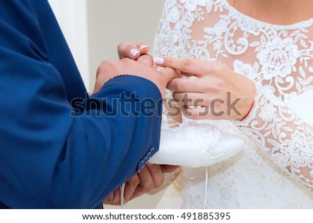 bride groom wears a wedding ring on the wedding ceremony
