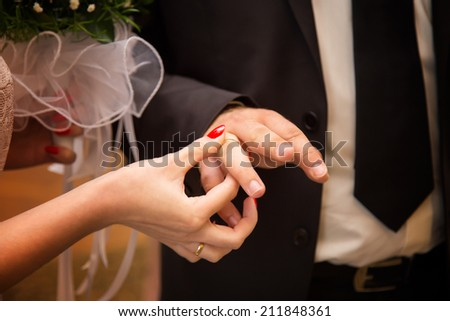 bride groom wears the ring wedding - stock photo