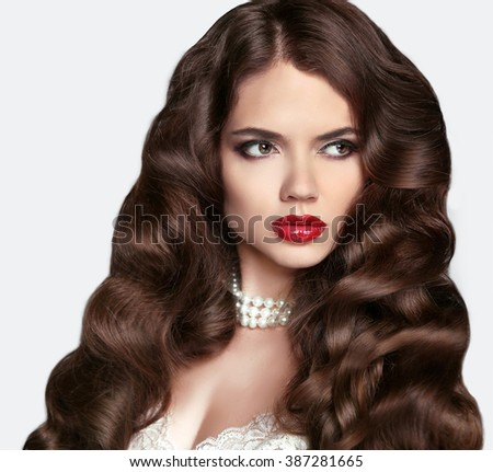 Bride Hairstyle. Healthy hair. Makeup. Beautiful brunette girl with long wavy hair style and Red lips. Elegant lady with jewelry. Wedding.  - stock photo