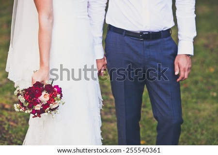 Bride hold groom by the hand and wedding bouquet. Focus on wedding flower bouquet. Crop by chest and legs. Bride in wedding dress, groom wears classic clothes. Vintage style coloring - stock photo