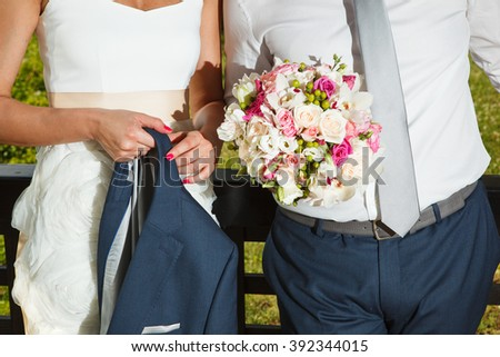 Bride hold his coat and groom hold her bouquet - stock photo