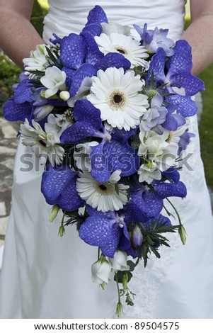 Bride holding a beautiful bouquet of flowers on her wedding day - stock photo