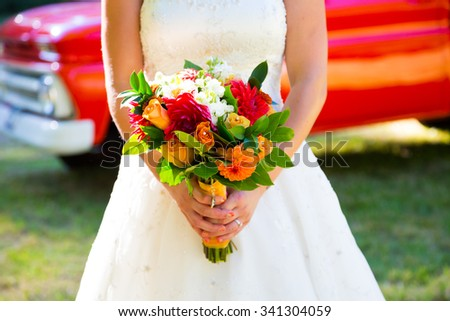 Bride holding a beautiful wedding bouquet before her ceremony. - stock photo