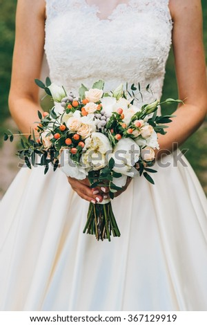 bride holding a bouquet of flowers in a rustic style, wedding bouquet
