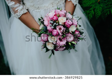 Bride holding a bridal bouquet made of rose