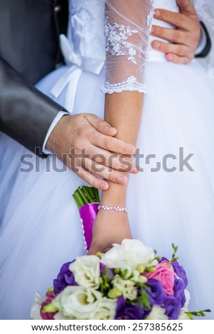 bride holding a wedding bouquet, groom gently embraces her hands - stock photo