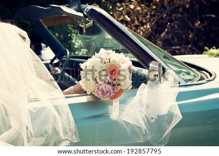 Bride Holding a Wedding Bouquet in an Vintage Car - stock photo