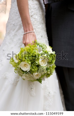 bride holding a wedding bouquet of white roses - stock photo