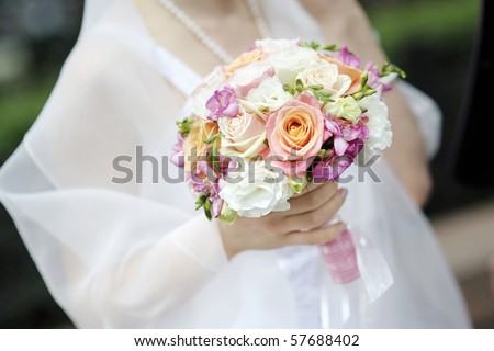 Bride holding beautiful pink wedding flowers bouquet
