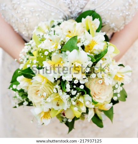 Bride holding beautiful yellow wedding flowers bouquet  - stock photo