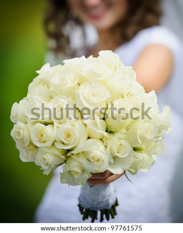 Bride holding bouquet of flowers - stock photo