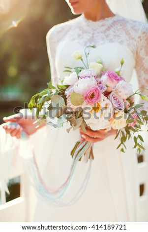 bride holding bouquet of peonies and roses