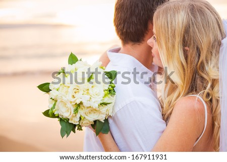 Bride holding bouquet of white flowers gazing at the ocean into the sunset - stock photo