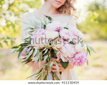 bride holding bouquet with roses and peonies