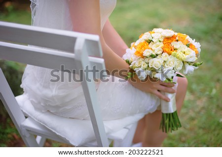 Bride holding bridal bouquet on her knees. - stock photo