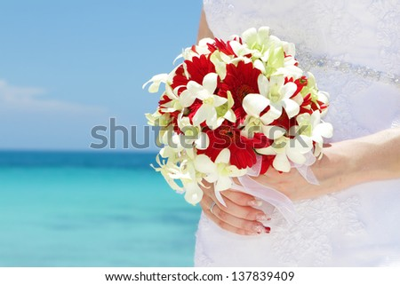 bride holding bridal bouquet on natural sea background, wedding on tropical beach - stock photo