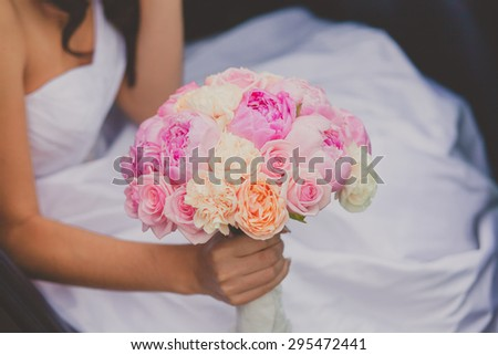 Bride holding bright wedding peony bouquet. Wedding details
