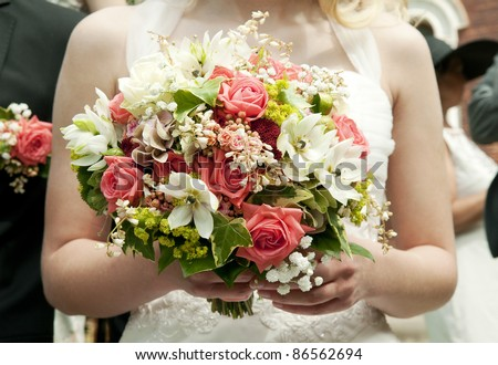 bride holding bunch of flowers at a wedding - stock photo