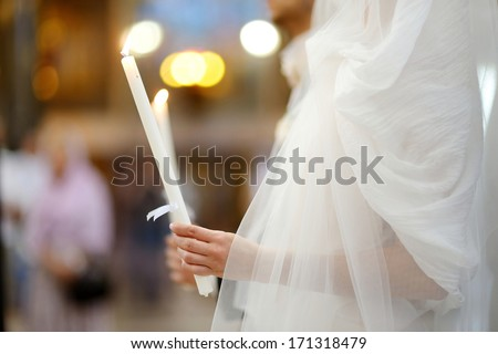 Bride holding candle during an orthodox wedding ceremony - stock photo