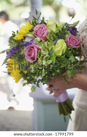 Bride holding colorful wedding bouquet against gown