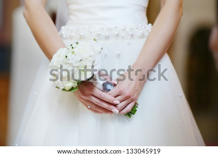 Bride holding flowers at the wedding ceremony in church - stock photo