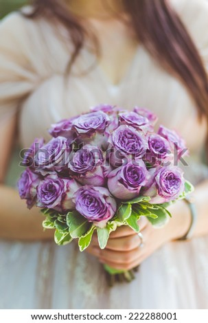Bride holding her bouquet of purple roses prepared for her wedding day - stock photo