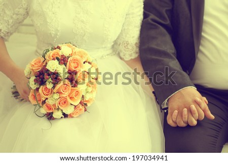 Bride holding her wedding bouquet made of roses  - stock photo