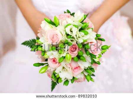 Bride holding orchid vivid flowers bouquet in hands - stock photo