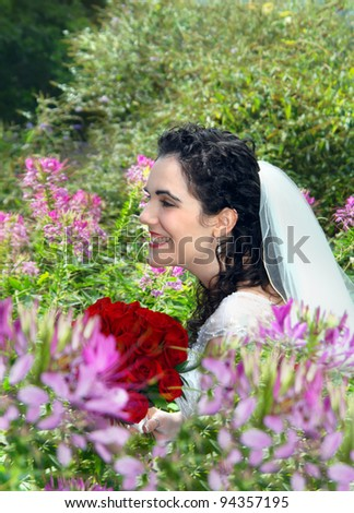Bride, holding red roses, is surrounded by pink flowers in an outdoor garden.  She is smiling and laughing and joy radiates from her face. - stock photo