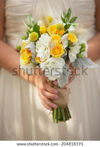Bride holding spring colored wedding bouquet of flowers - stock photo