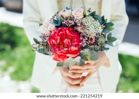 Bride holding wedding bouquet. Beautiful bouquet of roses and pe