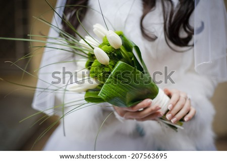 Bride holding wedding bouquet from white tulipes and golden-daisies. Selective focus (on a bouquet). - stock photo