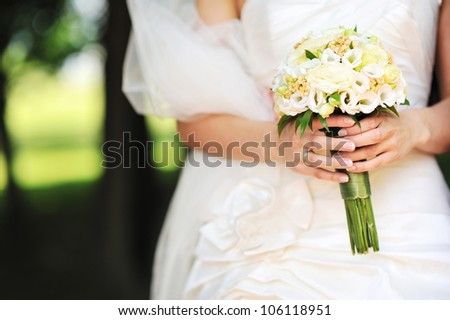 Bride holding wedding bouquet in hands - stock photo