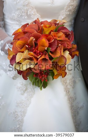 Bride holding wedding bouquet of calla lilies against dress - stock photo