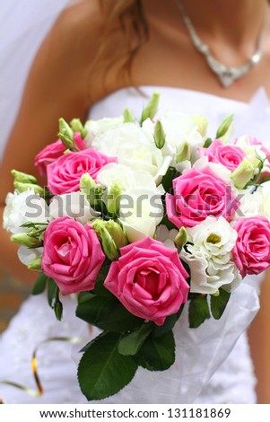 Bride holding wedding bouquet of pink and white roses close up - stock photo