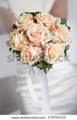 Bride holding wedding bouquet of  roses close up - stock photo