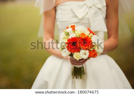 bride holding wedding bouquet of various flowers. - stock photo