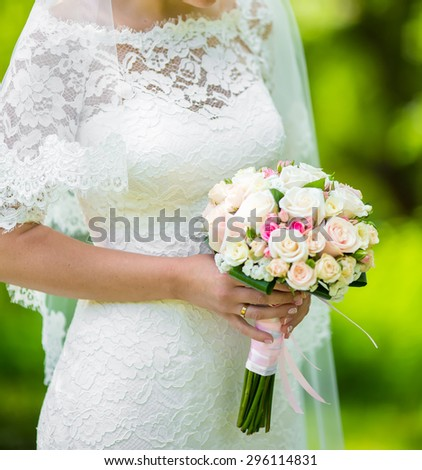 bride holding wedding bouquet of various flowers.