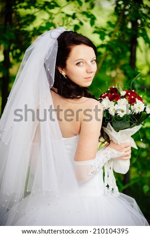 Bride holding wedding bouquet outside. Bride. Wedding hairstyle