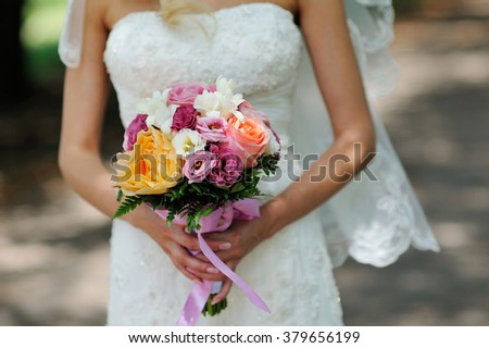 Bride Holding Wedding Bouquet with Orange white and Pink Flowers. - stock photo