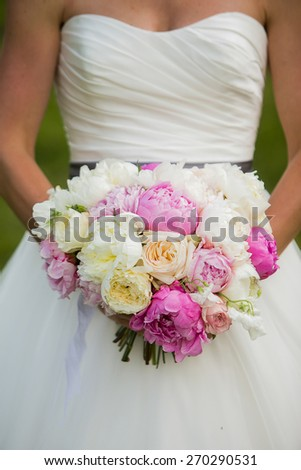 Bride holding wedding bouquet with Peonies, garden Roses, and Sweet pea flowers - stock photo
