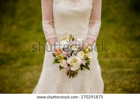 Bride holding wedding bouquet with Peonies, Tulips, Parrot Tulips, Roses, Dusty Miller, and Astilbe - stock photo