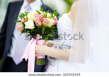 Bride holding wedding flowers roses bouquet  - stock photo
