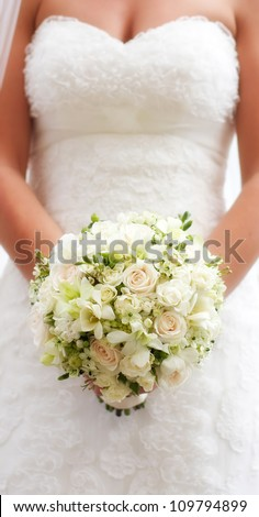 Bride holding white wedding bouquet of roses and love flower - stock photo