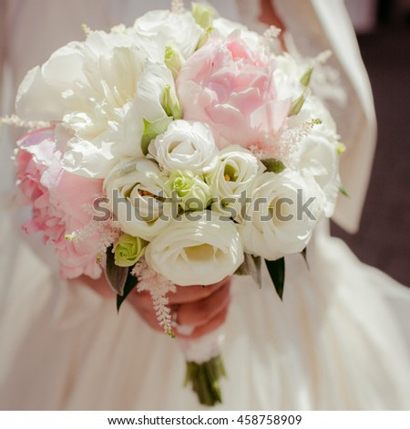 Bride holds a bouquet of white roses and peonies