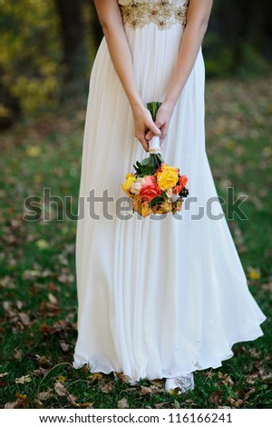bride holds a wedding bouquet of roses - stock photo