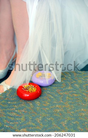 Bride holds her wedding dress up to be pinned and hemmed.  Stick pin caddies sit on bridal podium.  Pins have yellow tops. - stock photo
