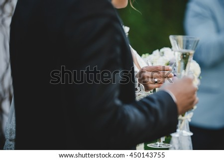 Bride holds in her tender hand with a wedding ring a champagne flute